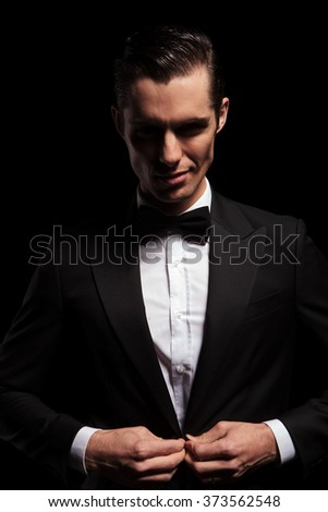 portrait of smiling elegant man posing in dark studio background while closing his black jacket and looking at the camera  - stock photo