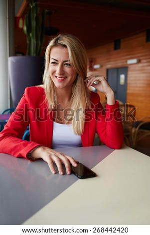 Portrait of smiling elegant woman sitting at cafe table looking away, blonde caucasian businesswoman looking happy and satisfied as she reads a text message on her smart phone - stock photo
