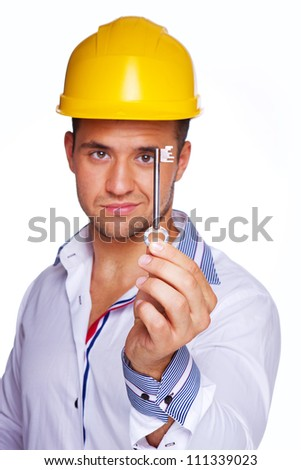 Portrait of smiling engineer posing in studio in helmet with key