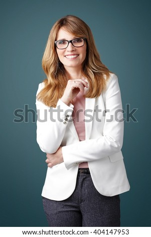 Portrait of smiling executive businesswoman standing at isolated background.