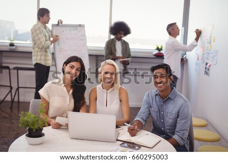 Portrait of smiling executives sitting while colleagues planning in creative office