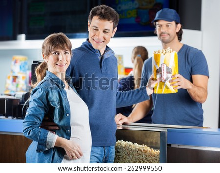 Portrait of smiling expectant couple taking popcorn from male seller at cinema concession counter - stock photo