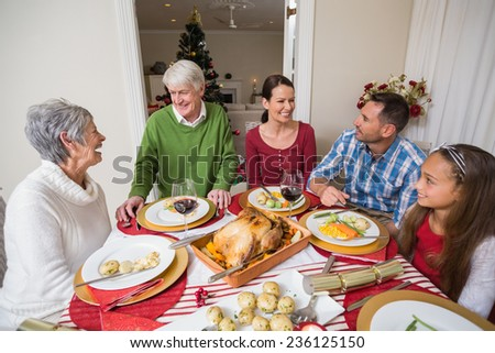 Portrait of smiling family at christmas at home in the living room - stock photo