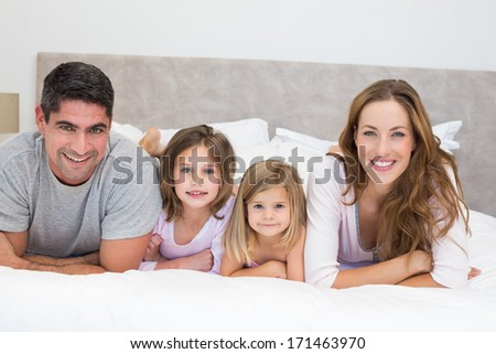Portrait of smiling family in bed