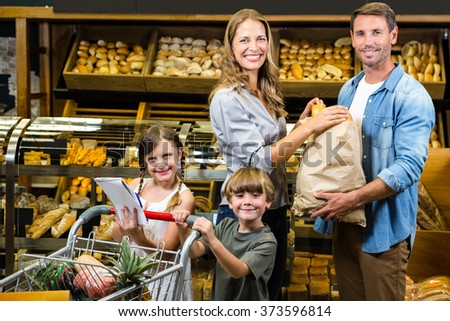 Portrait of smiling family in grocery store - stock photo