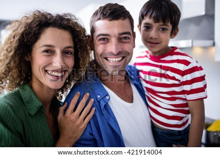 Portrait of smiling family in kitchen - stock photo