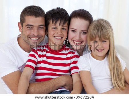 Portrait of smiling family in living-room sitting on sofa together