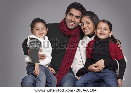 Portrait of smiling family over grey background - stock photo