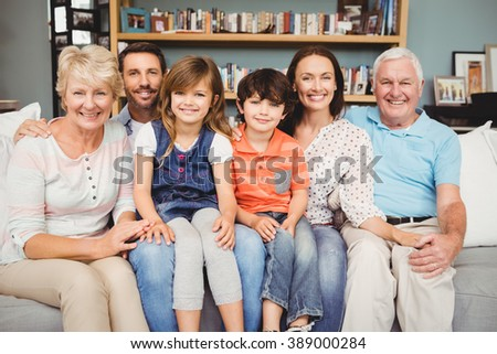 Portrait of smiling family sitting on sofa at home - stock photo