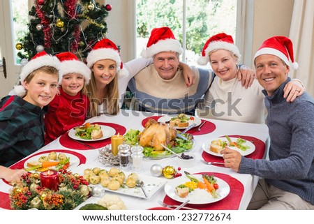 Portrait of smiling family sitting together at christmas dinner at home in the living room - stock photo
