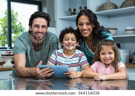 Portrait of smiling family using tablet in the kitchen - stock photo