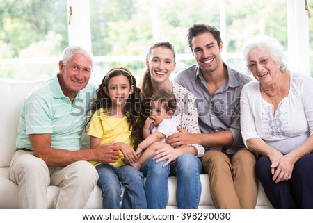 Portrait of smiling family with baby while sitting on sofa at home - stock photo