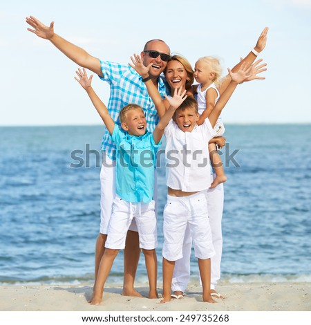 Portrait of smiling family with children having fun on the sunny beach with raised hands. - stock photo