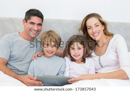 Portrait of smiling family with digital tablet in bed