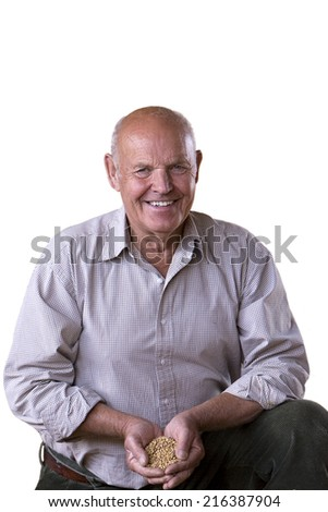 Portrait of smiling farmer cupping wheat grains, cut out - stock photo