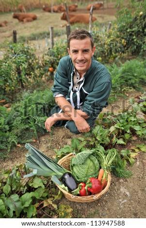 Portrait of smiling farmer in vegetable garden - stock photo