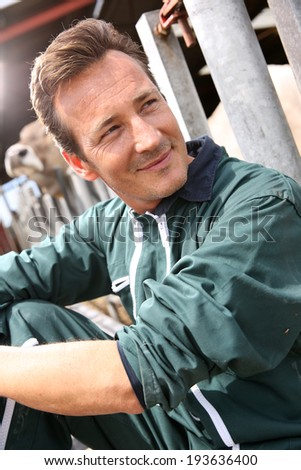 Portrait of smiling farmer sitting by barn - stock photo
