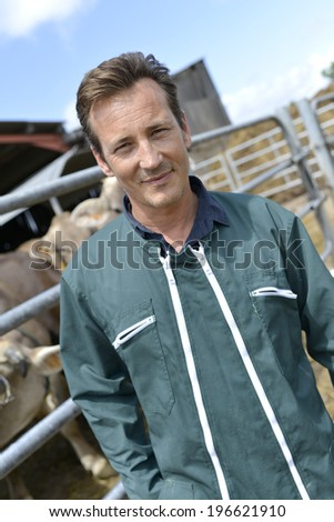 Portrait of smiling farmer standing by barn - stock photo