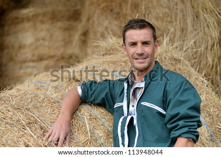 Portrait of smiling farmer standing by haystacks