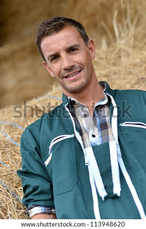 Portrait of smiling farmer standing by haystacks - stock photo
