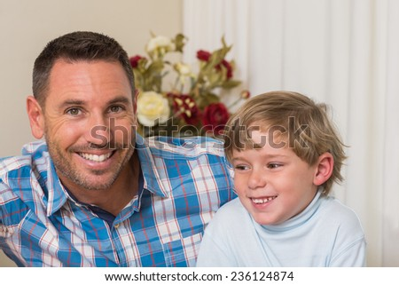 Portrait of smiling father and his son at home in the living room - stock photo