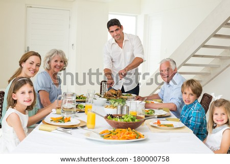 Portrait of smiling father serving meal to family at dining table - stock photo