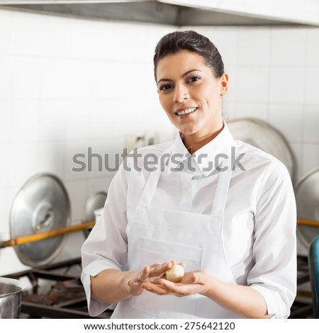 Portrait of smiling female chef holding pasta dough ball in commercial kitchen