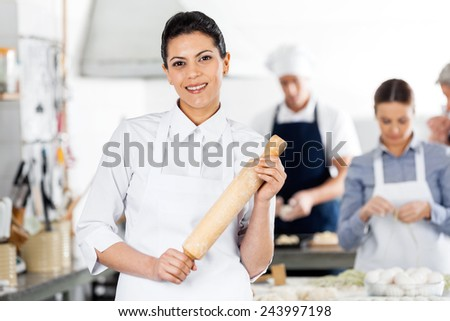 Portrait of smiling female chef holding rolling pin while colleagues preparing pasta at commercial kitchen - stock photo