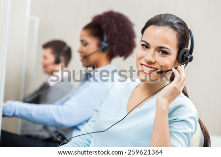 Portrait of smiling female customer service agent wearing headset with colleagues working in background at office - stock photo