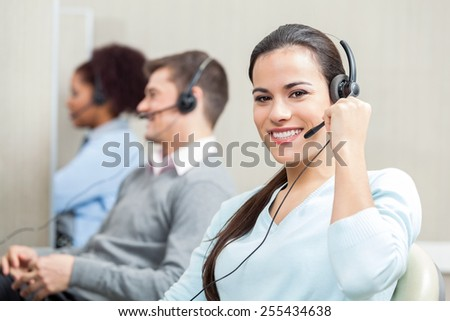 Portrait of smiling female customer service executive with colleagues in background at office - stock photo