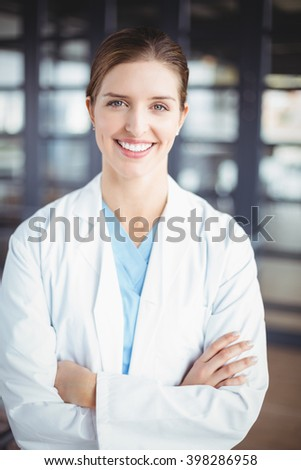 Portrait of smiling female doctor with arms crossed while standing in hospital