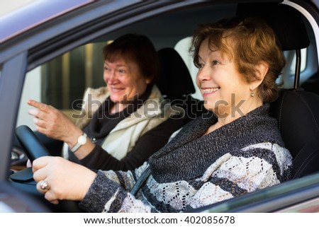 Portrait of smiling female elderly driver and her friend in car - stock photo