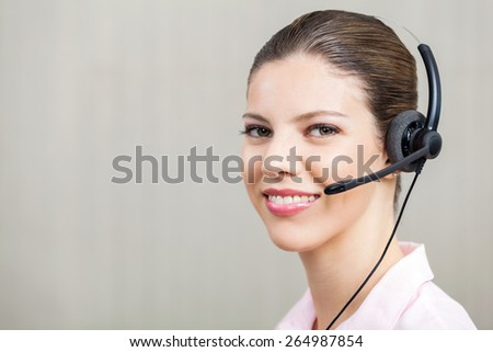 Portrait of smiling female employee wearing headset at call center - stock photo