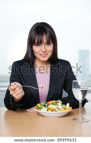 Portrait of smiling female executive having fresh vegetable salad in office - stock photo