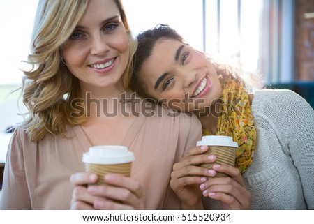 Portrait of smiling female friends sitting together and having coffee in cafeteria