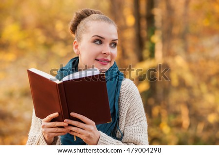 Portrait of smiling female in the golden forest reading a book