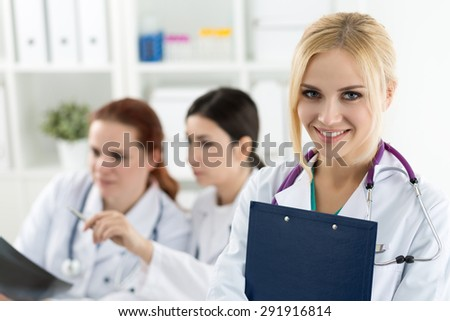 Portrait of smiling female medicine doctor holding blue document folder with two colleagues looking at x-ray picture at background. Healthcare and medicine concept. - stock photo
