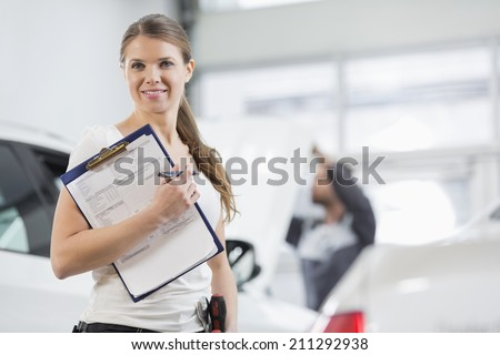 Portrait of smiling female repair worker with clipboard in car workshop - stock photo