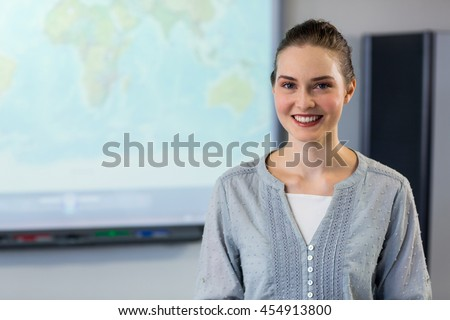 Portrait of smiling female teacher standing against projector screen in classroom - stock photo