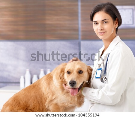 Portrait of smiling female vet with golden retriever at clinic. - stock photo