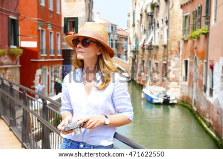 Portrait of smiling female with vintage camera discovering Venice.