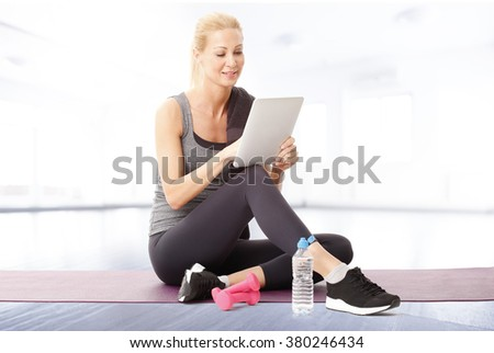 Portrait of smiling fit woman using digital tablet while sitting at yoga mat after fitness workout.  - stock photo