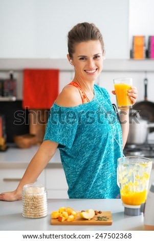 Portrait of smiling fitness young woman with glass of pumpkin smoothie - stock photo