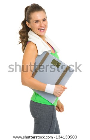 Portrait of smiling fitness young woman with scales - stock photo