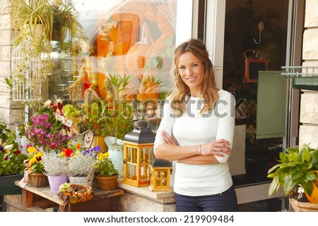 Portrait of smiling florist standing in front of flower shop's facade. Small business. - stock photo