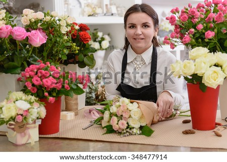 Portrait of smiling florist standing near the table wrapping the flowers in the shop