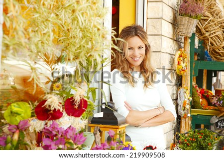 Portrait of smiling flower shop owner standing in front of shop window. Small business. - stock photo