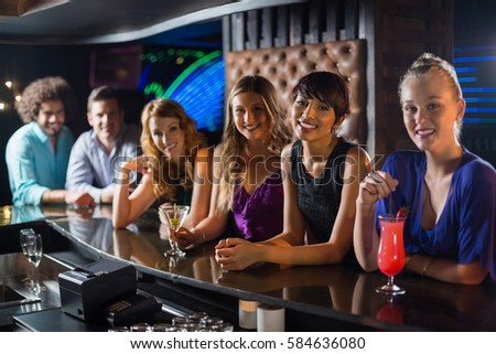 Portrait of smiling friends standing together at bar counter in bar
