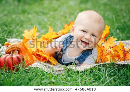 Portrait of smiling funny adorable blond Caucasian baby boy with blue eyes in tshirt and jeans romper lying on grass field meadow, yellow autumn fall leaves pumpkins. Halloween, Thanksgiving.