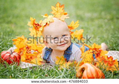 Portrait of smiling funny adorable blond Caucasian baby boy with blue eyes in tshirt and jeans romper with autumn fall leaves on his head lying on grass. Halloween, Thanksgiving seasonal concept.